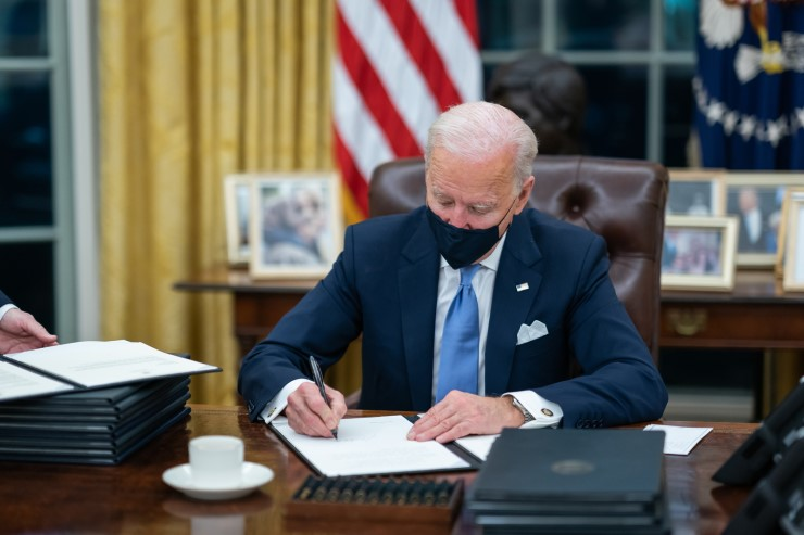 President Joe Biden signs 17 executive orders on Inauguration Day in the Oval Office.