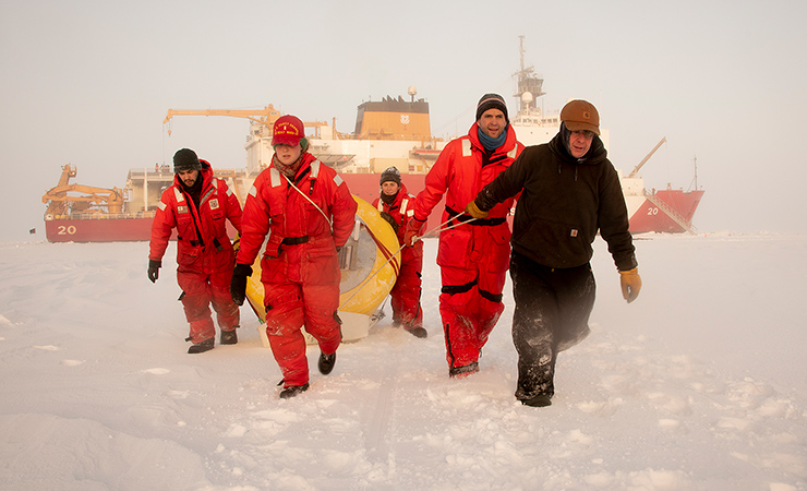Crew from the U.S. Coast Guard Cutter Healy pull a buoy across Arctic sea ice in 2018.