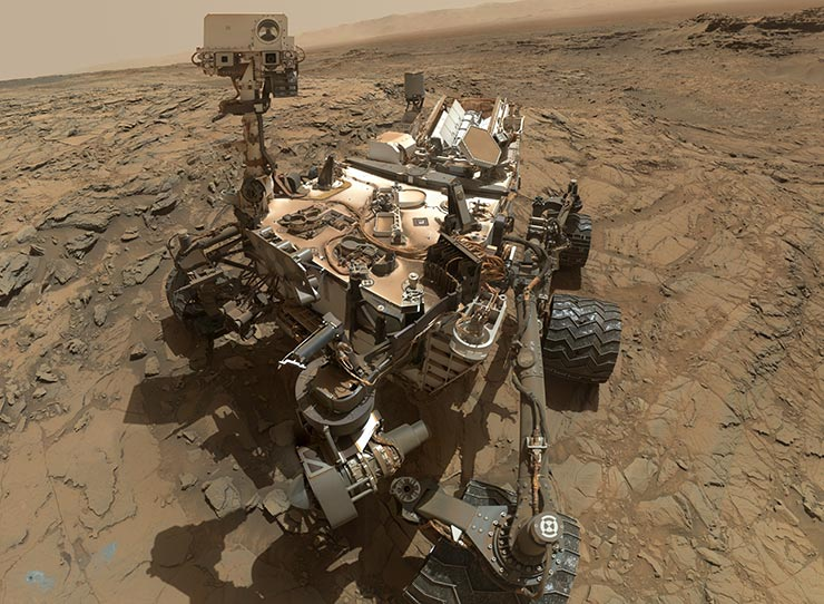 In this image, composed of dozens of photographs, the Mars Curiosity rover is pictured next to a drill hole it has made in the martian surface, seen in the lower left-hand corner.