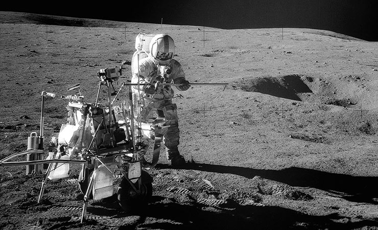 Apollo 14 astronaut Alan Shepard assembles equipment on the lunar surface in February 1971.