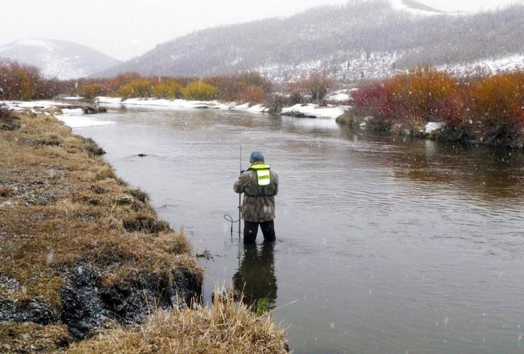 A USGS hydrologic technician measures streamflow in the Blackfoot River near Henry, Idaho,in 2014.