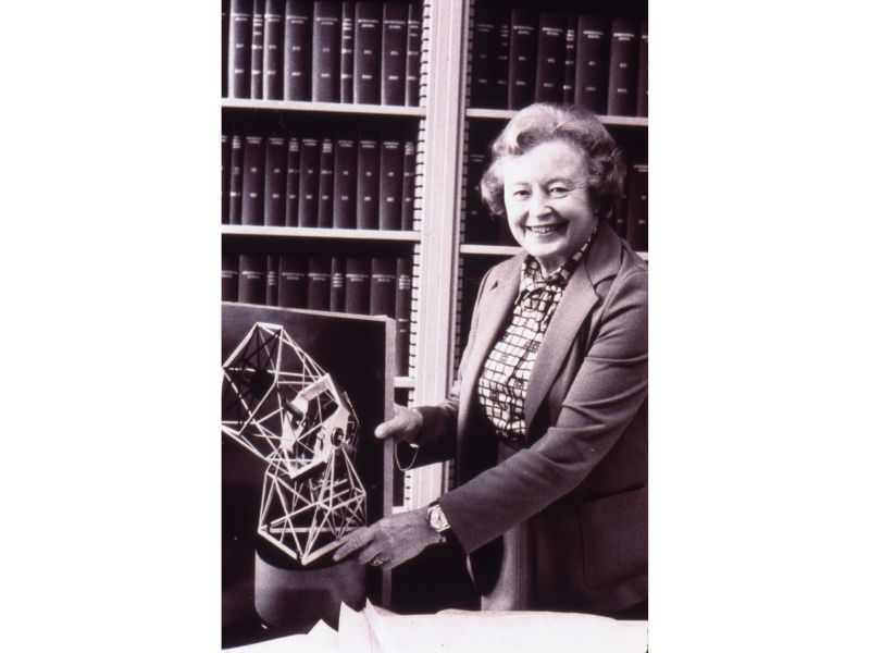 Margaret Burbidge holding a photograph of a model of a telescope.