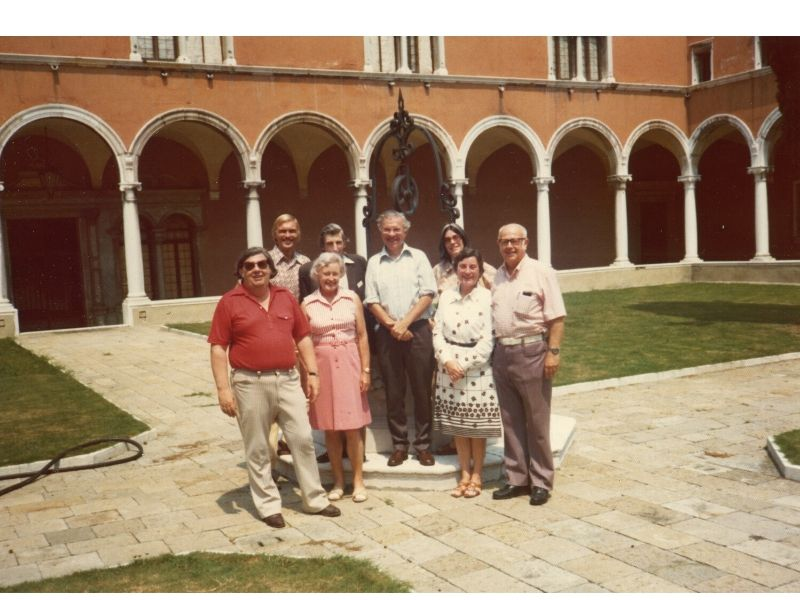 Group portrait of Margaret and Geoffrey Burbidge (front left), William Fowler (front right), Fred, Barbara, and Elizabeth Hoyle (center), and Donald Clayton and Martin Rees (rear left) at the monastery on the Isola St. George in Venice, Italy, 1975.