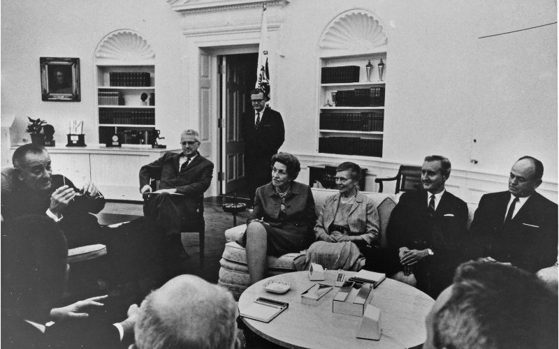 A group of people including Charlotte Moore Sitterly sit with President Johnson.