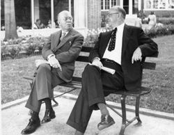 Karl Darrow (left) sitting on bench outdoors talking with Henry Barton (right) at American Physical Society (APS) Meeting.