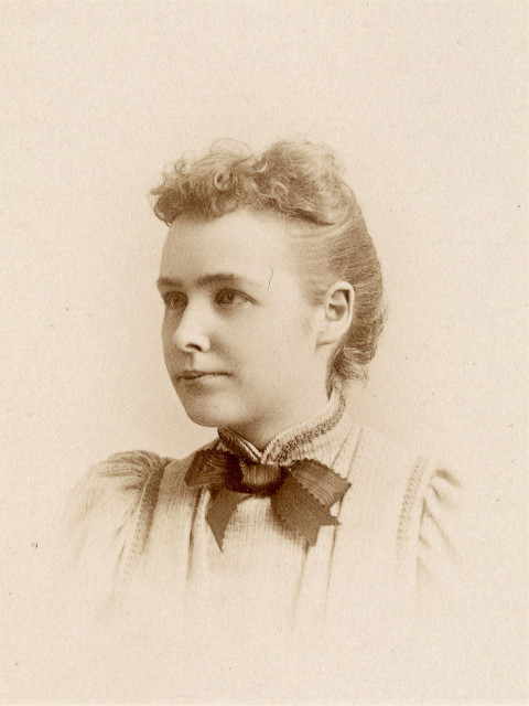 Portrait of a young woman in three-quarter profile wearing a light-colored dress with a dark bow tie circa the late 1800s. Her hair is pulled back except for short curly bangs in the front