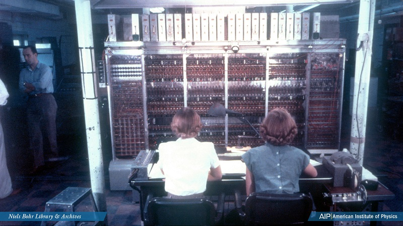 Two women sitting at a computer, seen from the back