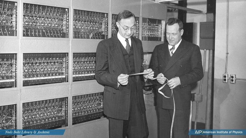 Professor Abraham H. Taub and Professor Ralph E. Meagher examine an ILLIAC I tape.