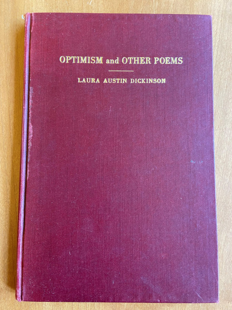 """a slim book, maybe a centimeter deep, with a red cover and embossed gold lettering reading """"Optimism and Other Poems"""" and """"Laura Dickinson"""""""