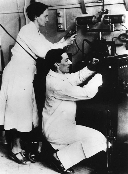 Irène and Frédéric Joliot-Curie working with equipment