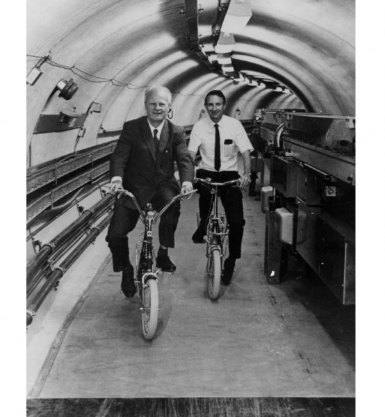 Hans Bethe and Boyce McDaniel ride bicycles in the Cornell Electron Storage Ring