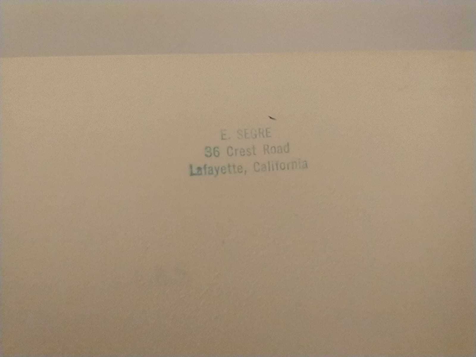 """Book owner's stamp with Emilio Segre corrected to """"Segrè."""" Address reads 36 Crest Road, Lafayette, California"""