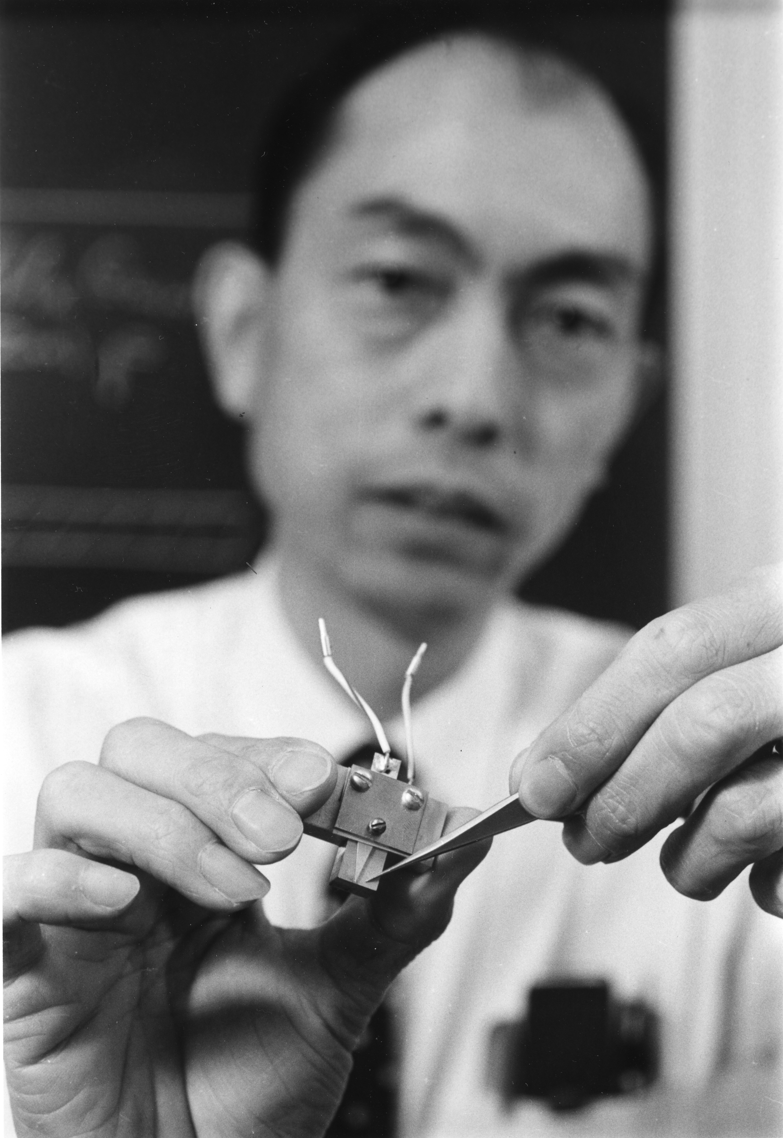 Izuo Hayashi, holding a heat absorbing device, points to the location of a new semiconductor laser.