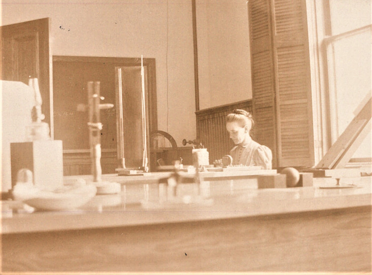 In this sepia photograph, the camera peaks over the top of a lab bench to capture Marcia Keith sits with head bent amidst laboratory equipment at Mount Holyoke College.