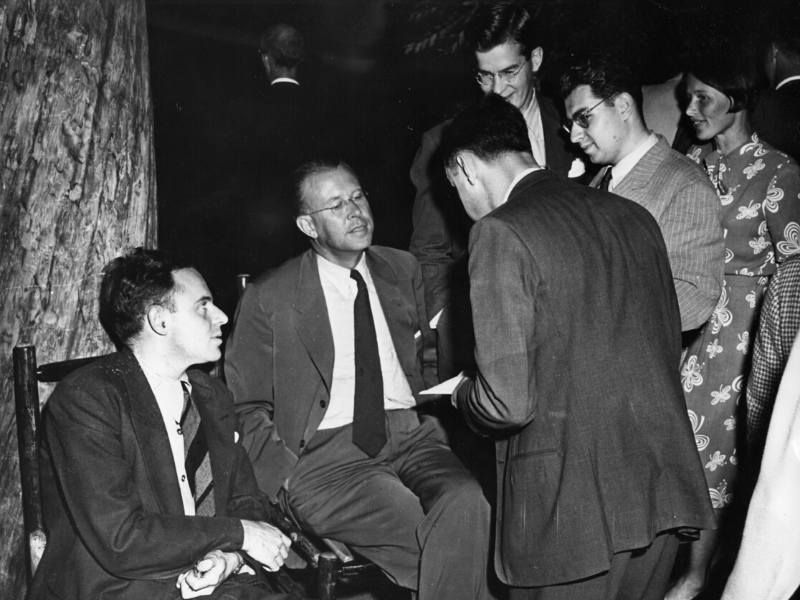 Five well-dressed men and one woman chat during a party. Morrison is one of two men seated at far left; the other stand.