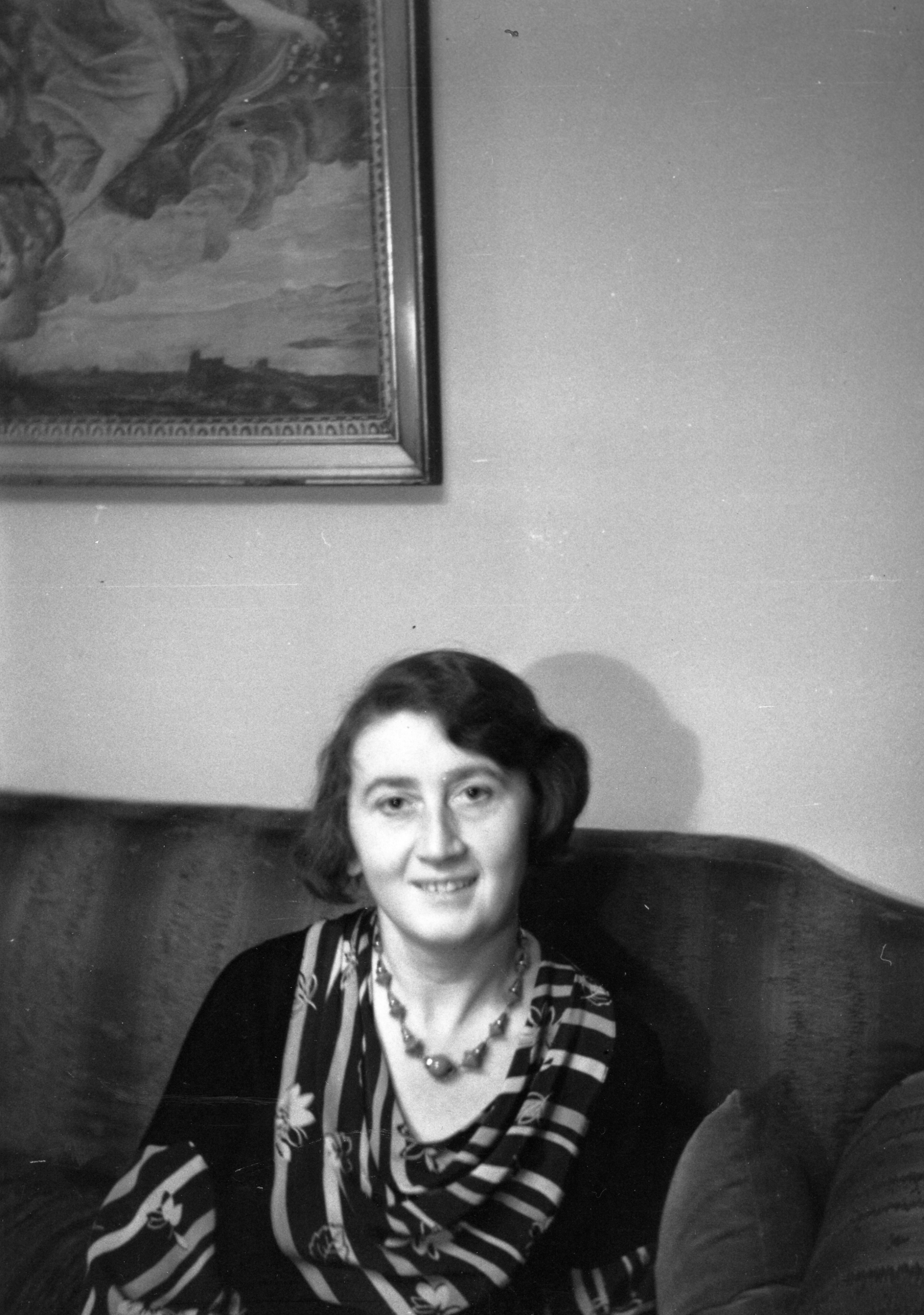 Informal portrait of Betty Schultz sitting on a sofa.