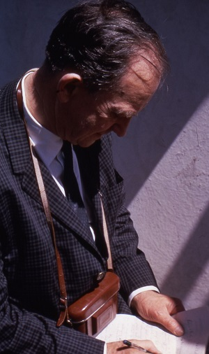 Image of Merle Tuve, with a camera around his neck, writing notes in 1966. AIP Emilio Segrè Visual Archives, John Irwin Slide Collection