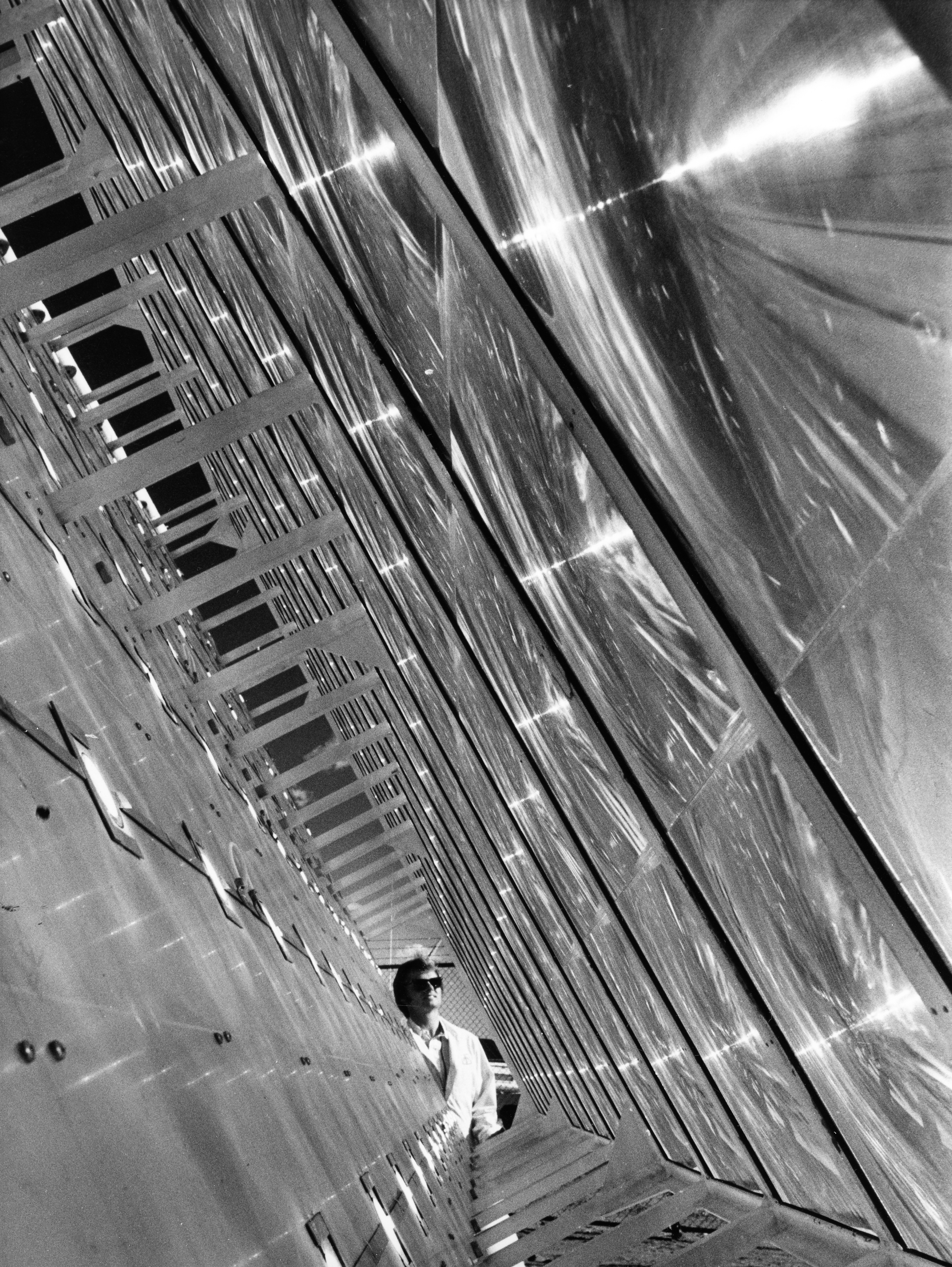 The photograph shows the space between a large concentrator array with a man in sunglasses standing behind the concentrator, but appearing between the space.