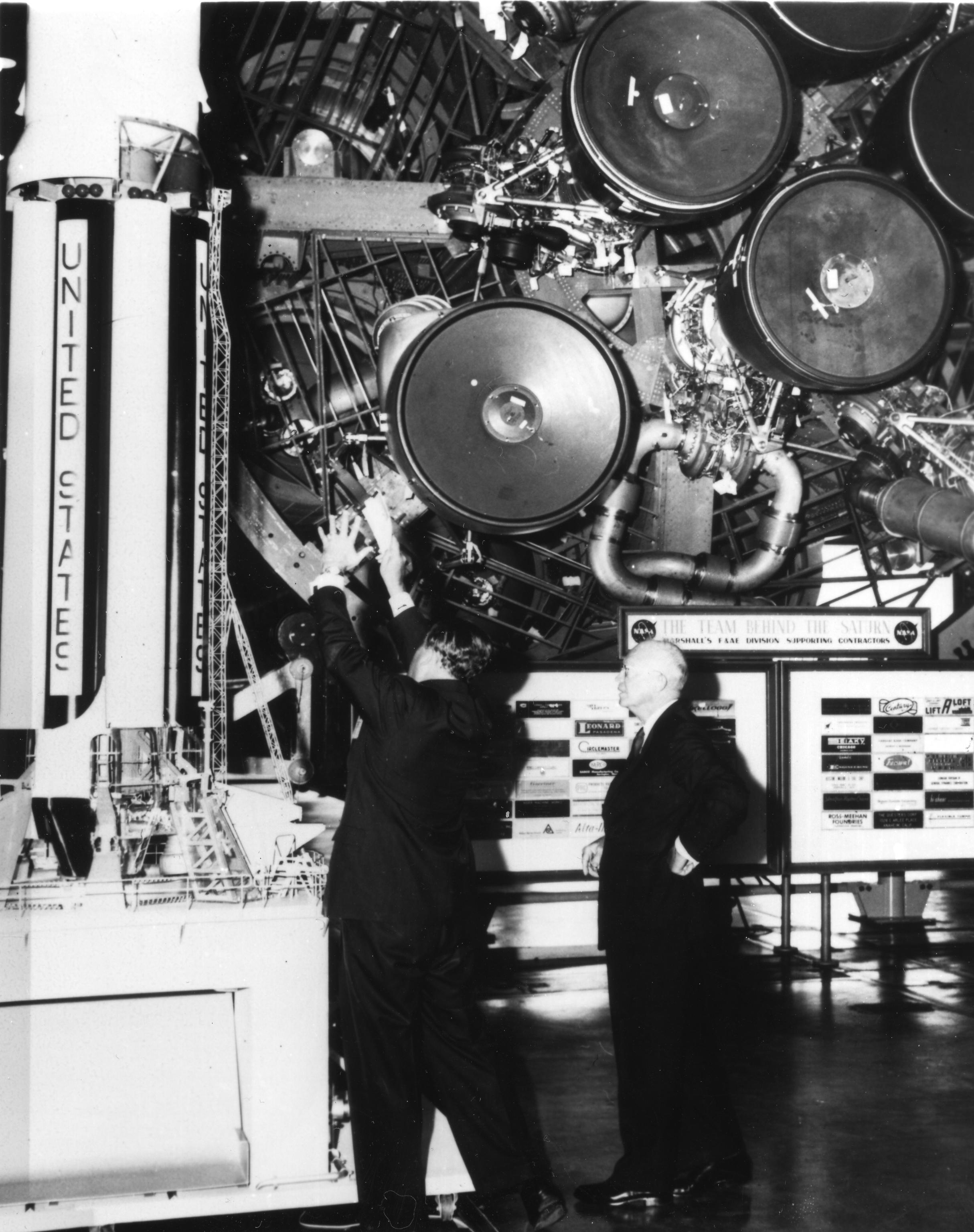 L-R: Wernher von Braun in Huntsville, Alabama showing Dwight D. Eisenhower how Saturn booster will work. Both stand next to a Saturn model..