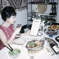 Telegdi Valentine G8 - Lia Telegdi, sits at their dining table holding a handmade dinner menu, December 26, 1966.