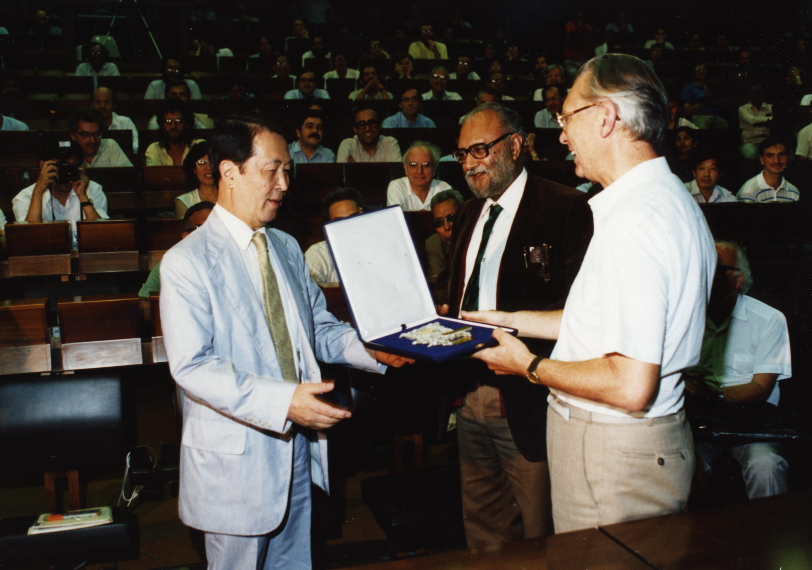 Yoichiro Nambu accepting award from Herwig Schopper and Abdus Salam.