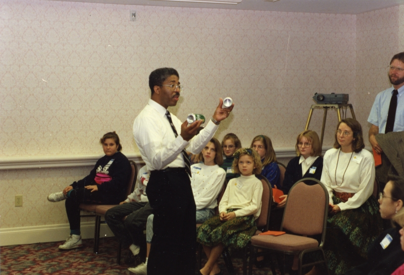 James Stith demonstrates to students holding two cans