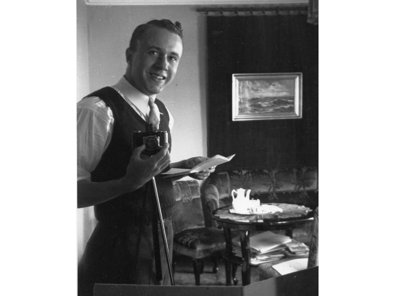 John Archibald Wheeler smiles with a camera.